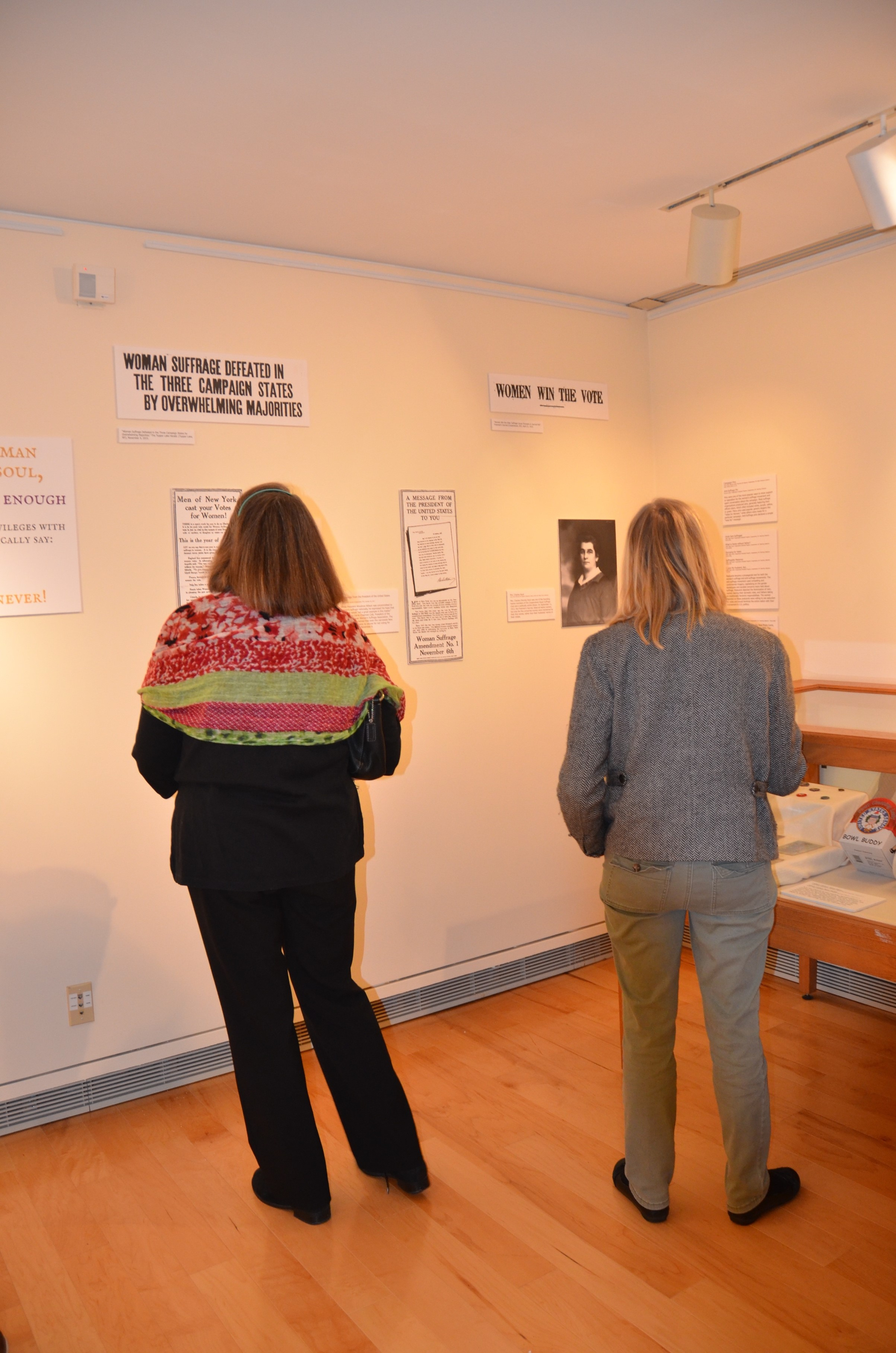 """Two community members at the opening reception for """"Conversations: Local Voices on Women's Suffrage."""""""