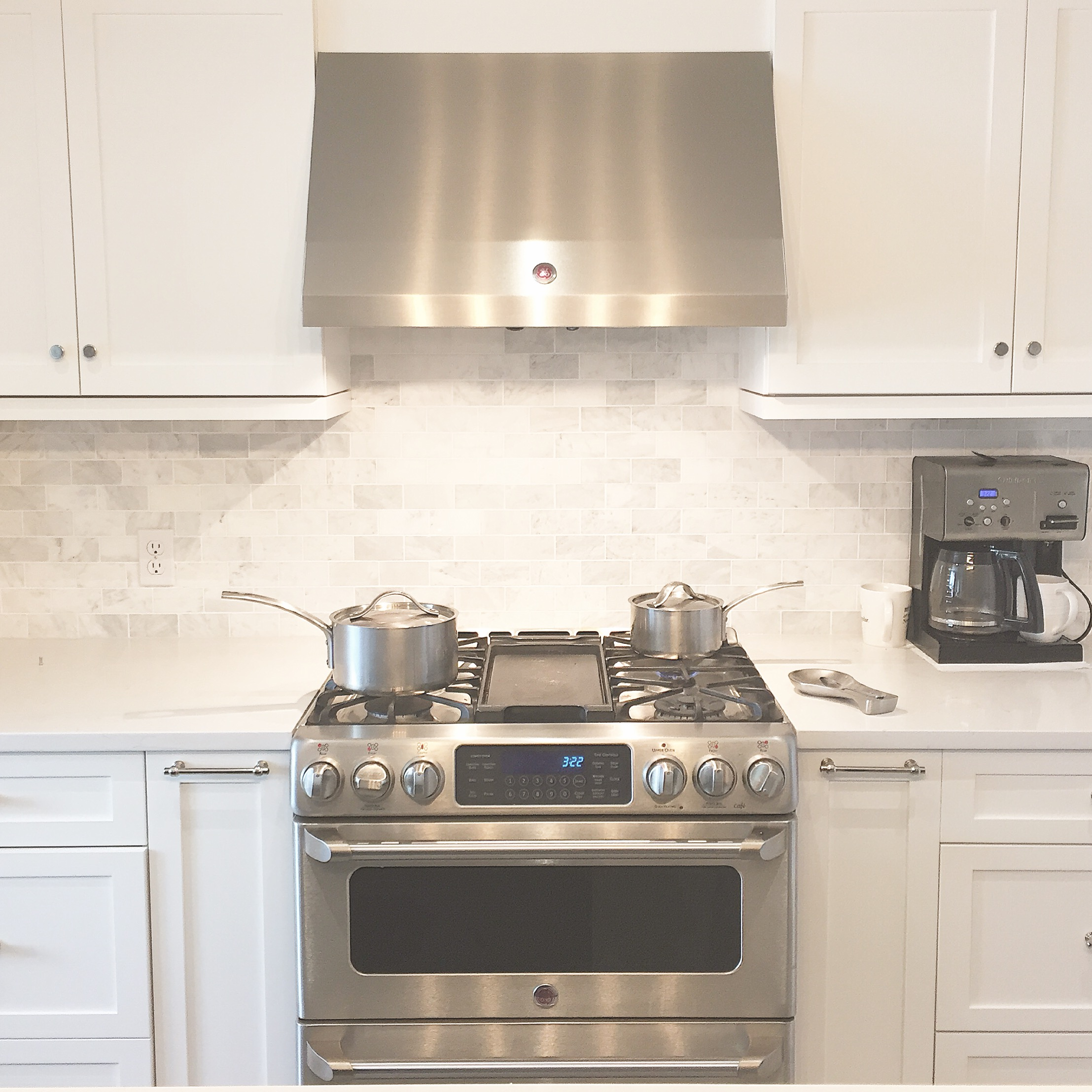 Simple white kitchen with identical cabinets on either side of the range.