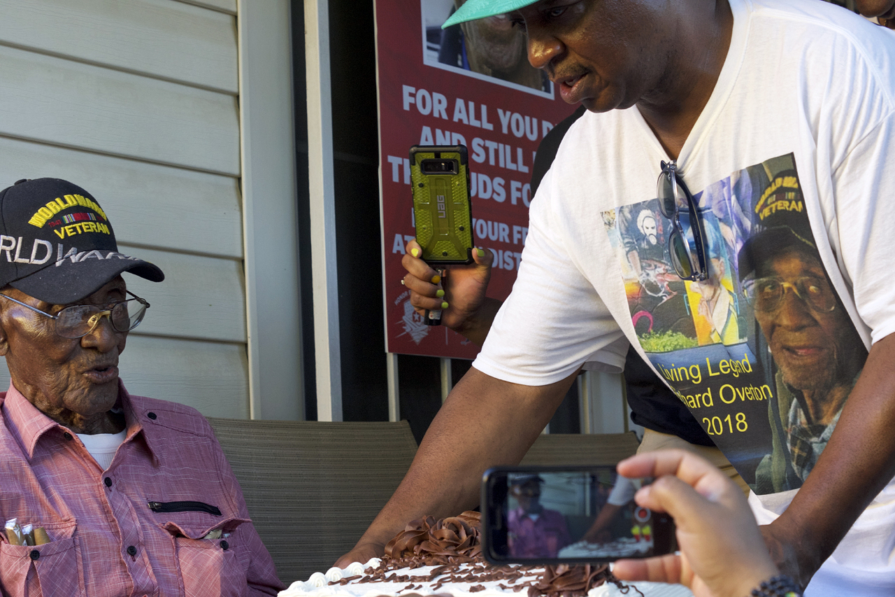 As celebrating Austinites look on from the front yard, longtime friend and caregiver Martin Wilford presents Richard Overton with his 112th birthday cake on Friday, May 11, 2018, at Overton's East Austin home.