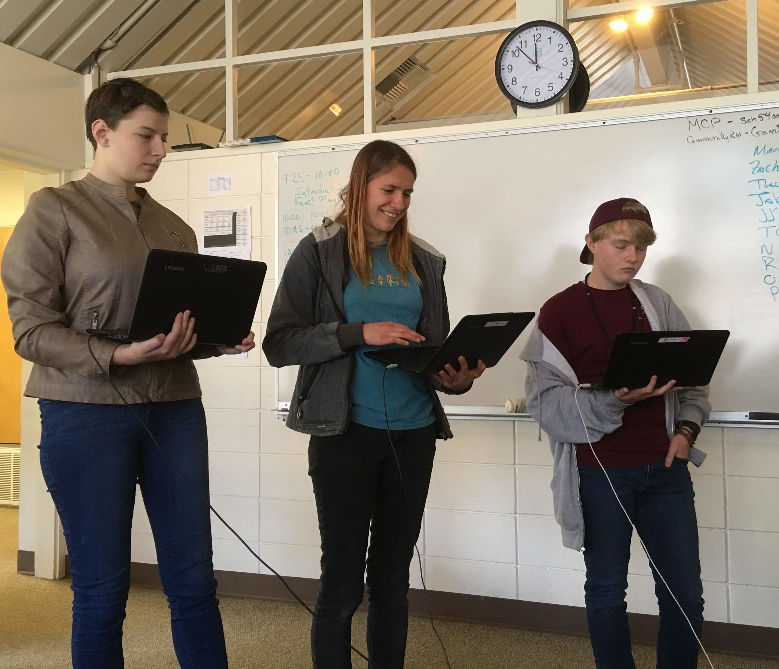 Three students giving a presentation to class