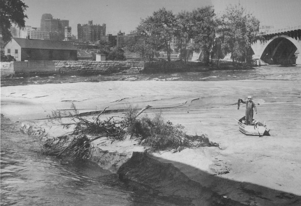 By the 1920s, the Mississippi river had become one of the world's best carp fishing hotspots. This angler, beached on sand flats below the 3rd Avenue bridge in Minneapolis, holds a carp recently caught in the river.