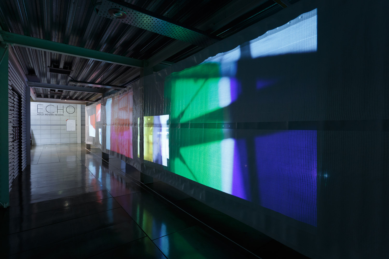Holly Rowan Hesson , Echo  (partial view), 2017, projection (140 photographs looped on six projectors), scaffold sheet, steel structure, webbing, lighting gels