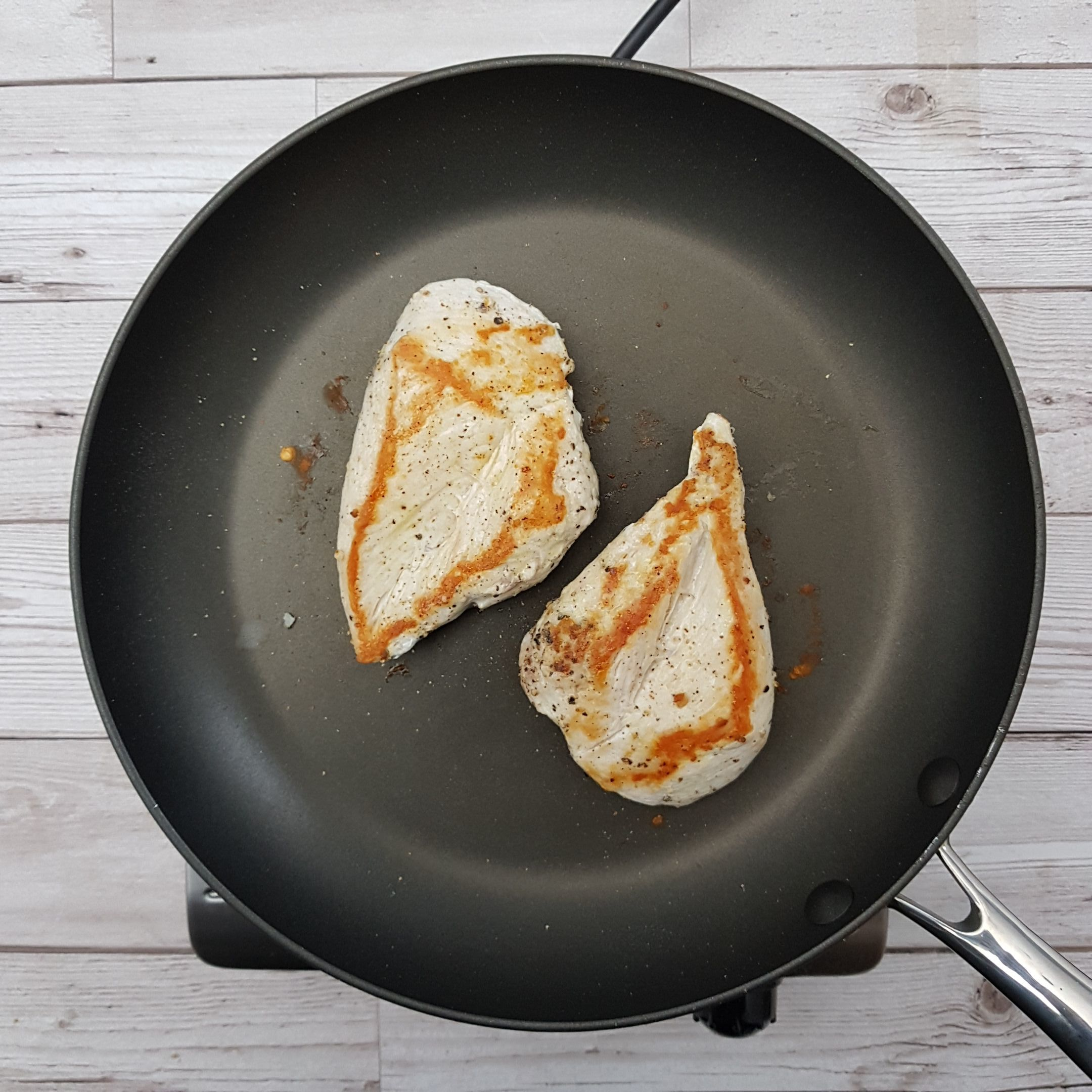 2.	Get a non-stick frying pan hot, and add the breasts. Reduce the heat to medium-low and cook for 6-7 minutes each side until the juices are clear and the meat is white all the way through