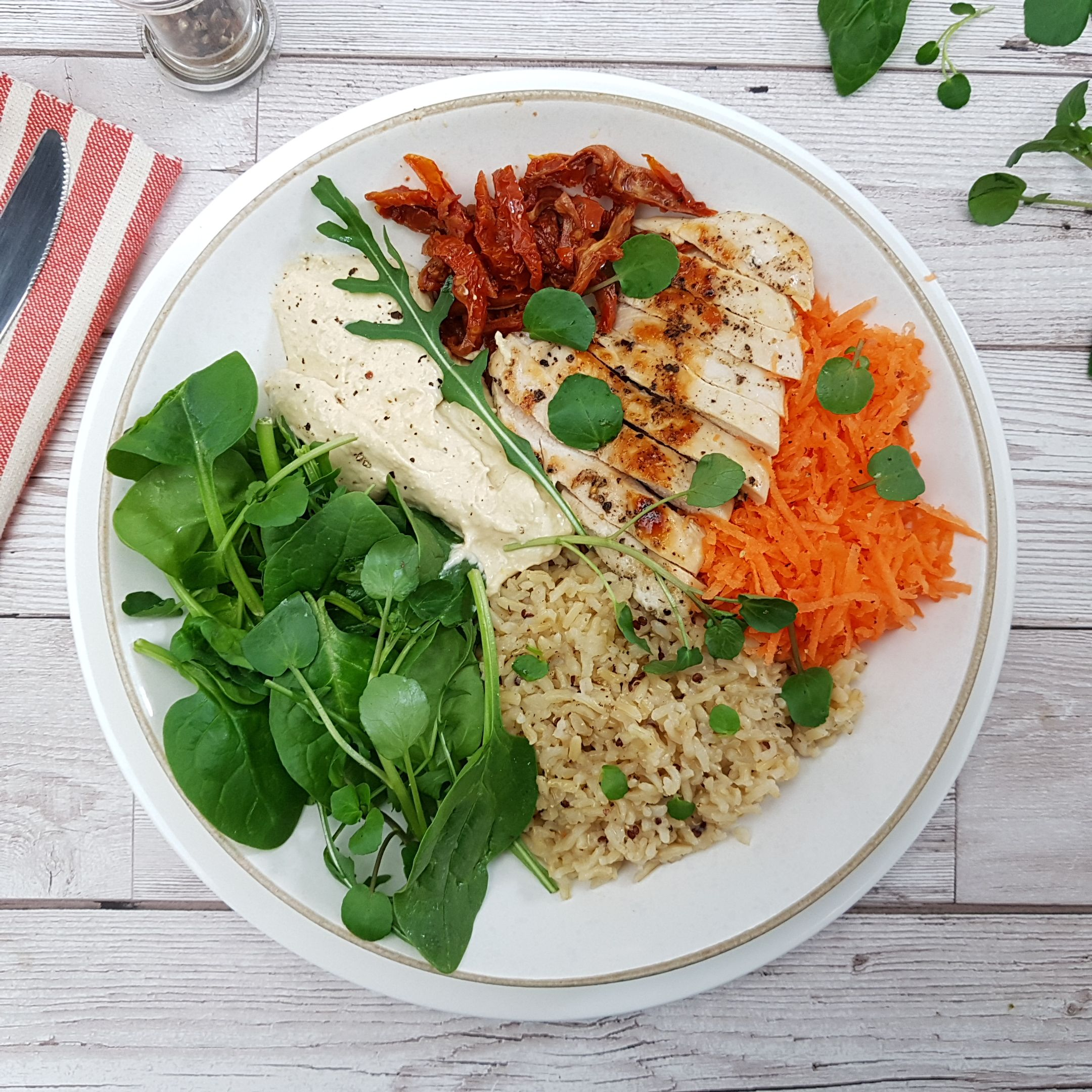 Slice the chicken breast and arrange the salad, rice, hummus, grated carrot and sundried tomatoes in two bowls