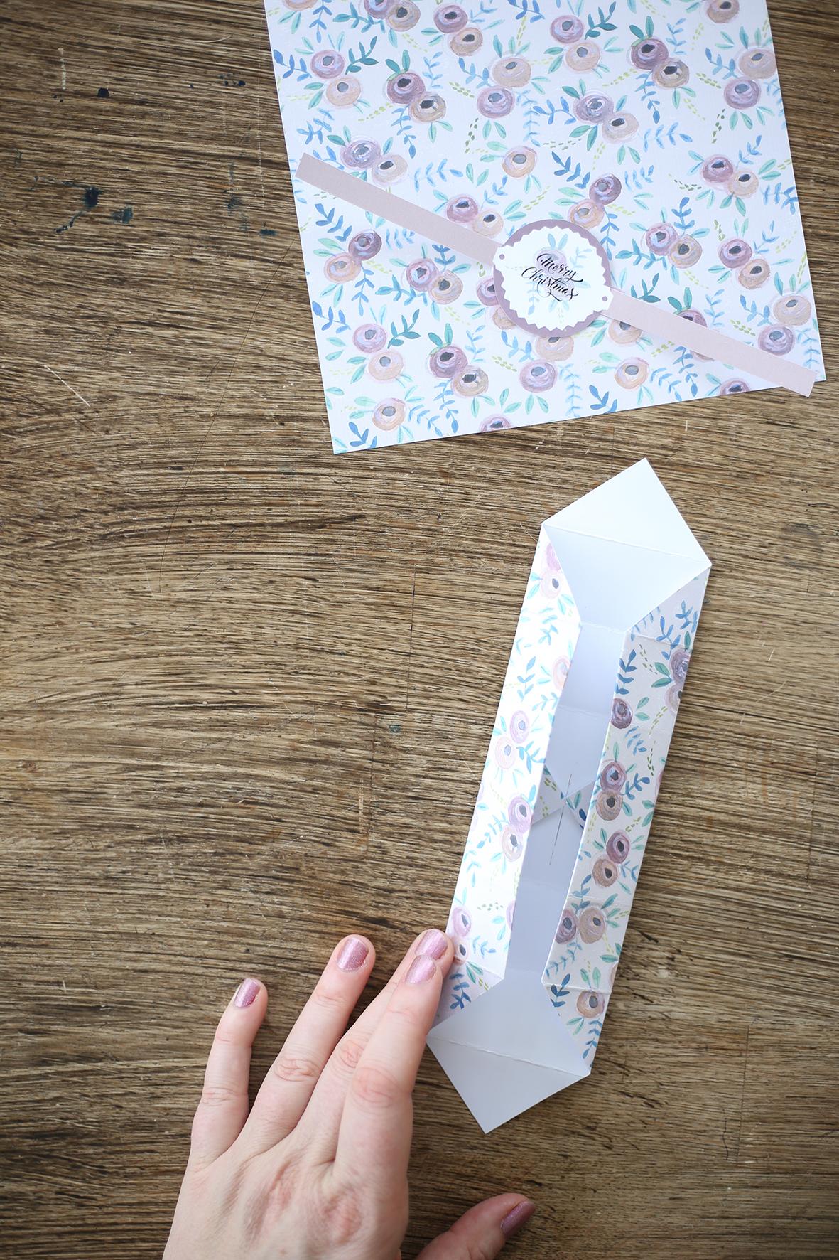 """5. Vik ut två av de motstående hörnen. I pappret har du nu """"vik"""" som markerar var hörnen i asken kommer att hamna."""