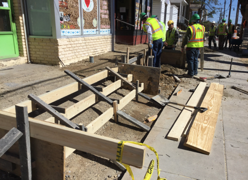 Contractor placing forms for ADA ramps and stairs leading to businesses.
