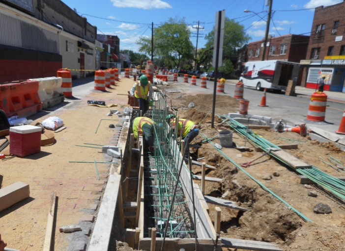 Capital Paving installing rebar's in seat wall footing in front of building #100.