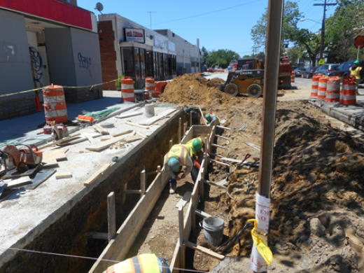 Forming footing for seat wall in front of building #116
