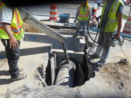 Pouring concrete around pipe connection pipe at CB #106