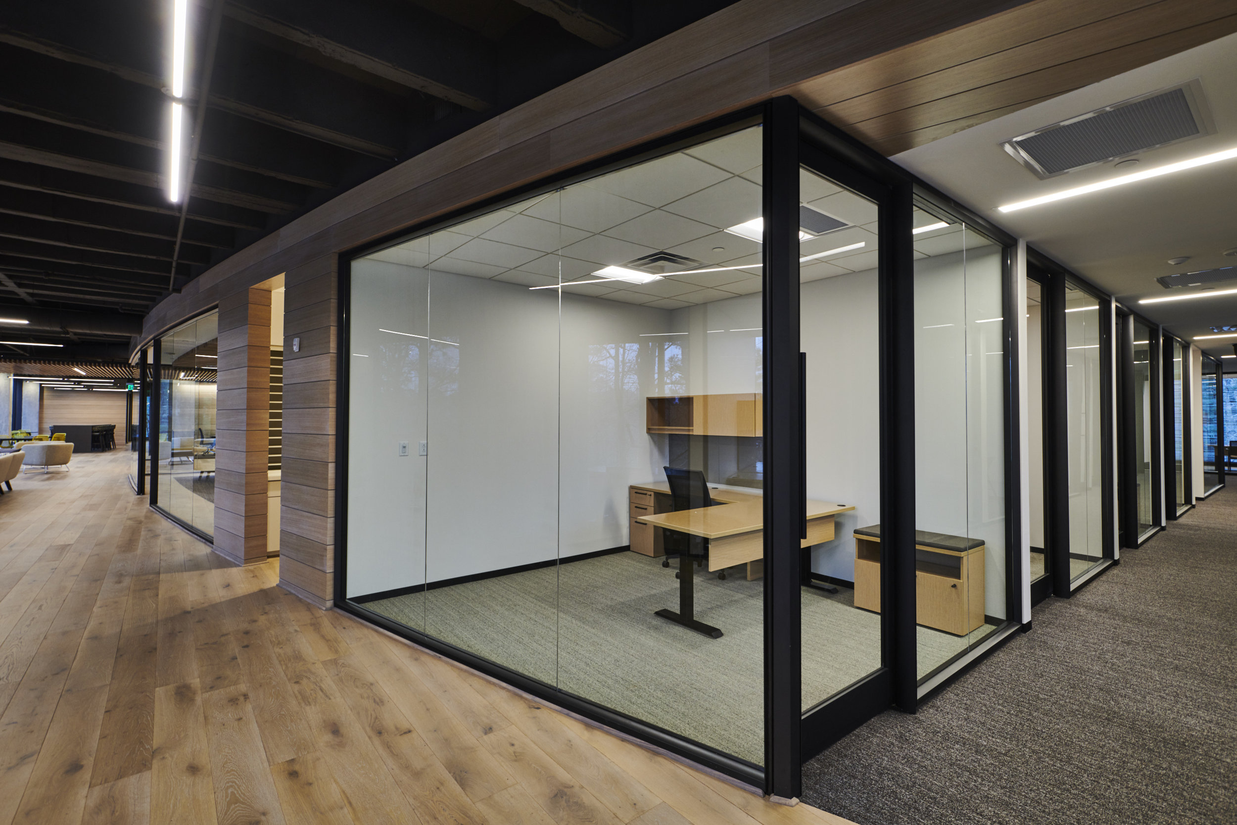 The interior finishes combine the company's formal side blended with the dynamic use of wood reflecting their specialization in timber investment. This synthesis is emphasized throughout the space with the use of wide plank oak walls and floors contrasting with the dark frames of the glass partitions.