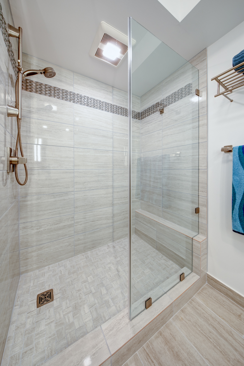 This bathroom used to have a bathtub. We ripped that out and installed a large walk-in shower. We call this a Tub-T0-Shower-Conversion. Most people of our clients are getting rid of their bathtubs these days. As you can see here, we were able to create a pretty large shower where the tub used to be. Clients wanted a shelf in the back to stack shampoo and conditioners instead of a more common soap cubby. It can be used as a bench as well. We decided to go with the fixed frameless glass panel, instead of a glass door. This gave them a more open feel, which is what they really wanted.