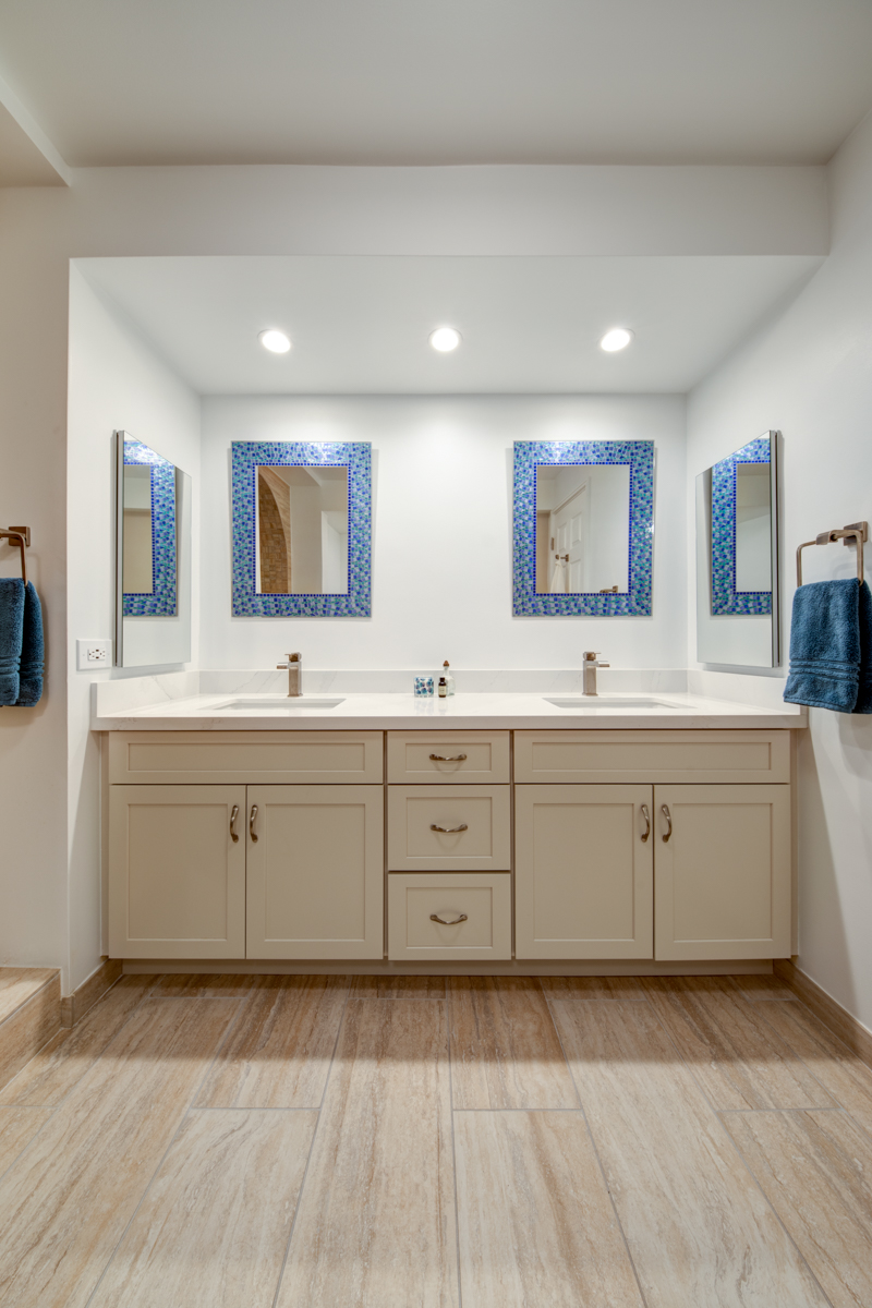 Because the walk-in shower and tub are so incredible, we kept it simple with the vanity area. You don't want to over do it. We went with off white shaker cabinets, with a quartz countertop and white square sinks. We added mirrored medicine cabinets on either side of the vanity. The clients were able to find the mirrors they loved and bought towels to match. We kept it simple and yet everything has clean straight lines, including the faucets.