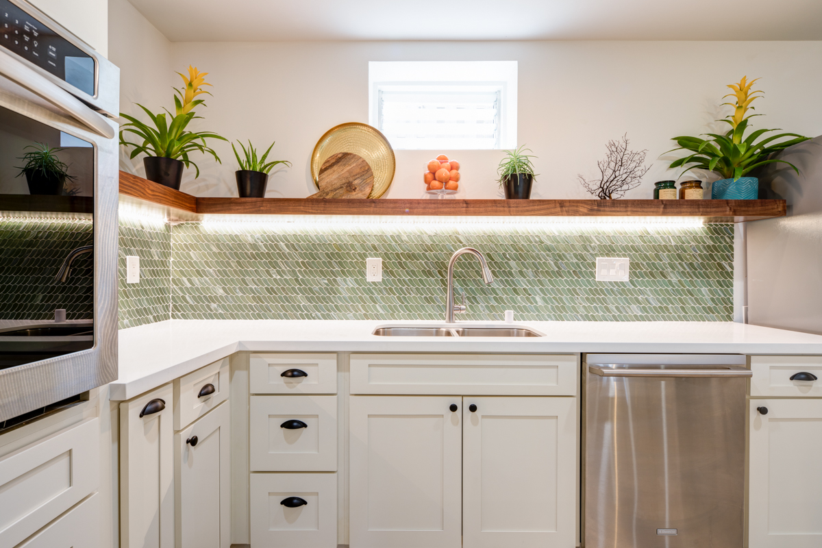Here you can see the feathered beach glass looking backsplash tile above the counter. We built a walnut shelf instead of doing upper cabinets. We wanted to put up decorations to give it a vacation feel. We chose a barn door to separate the bathroom and laundry area.
