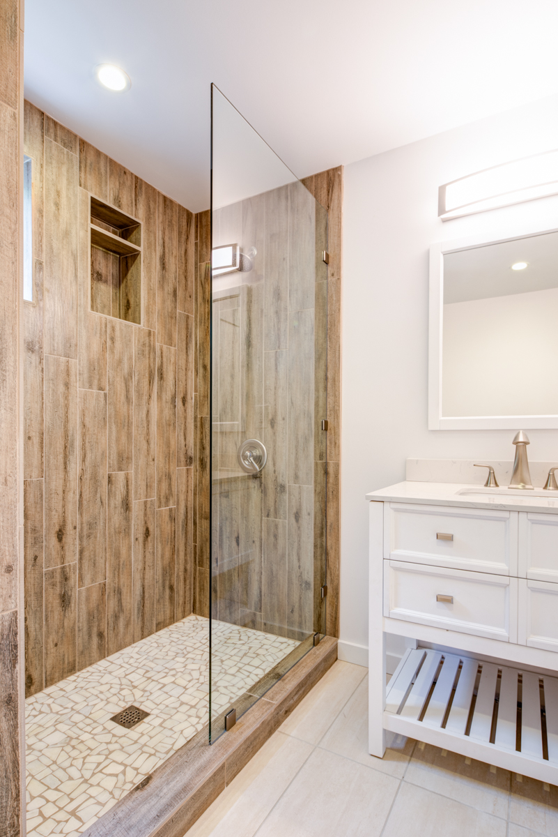 Keeping it simple, we did not use any accent tiles in this shower. The staggered wood porcelain tile compliments the beige floor tile and stone shower pan. Our shower design fits with the vacation feel of the rest of the home. We felt that a solid glass panel was enough rather than installing a full shower door system. This is one of our most popular bathrooms, and one of the simplest and least expensive ones we've ever done.