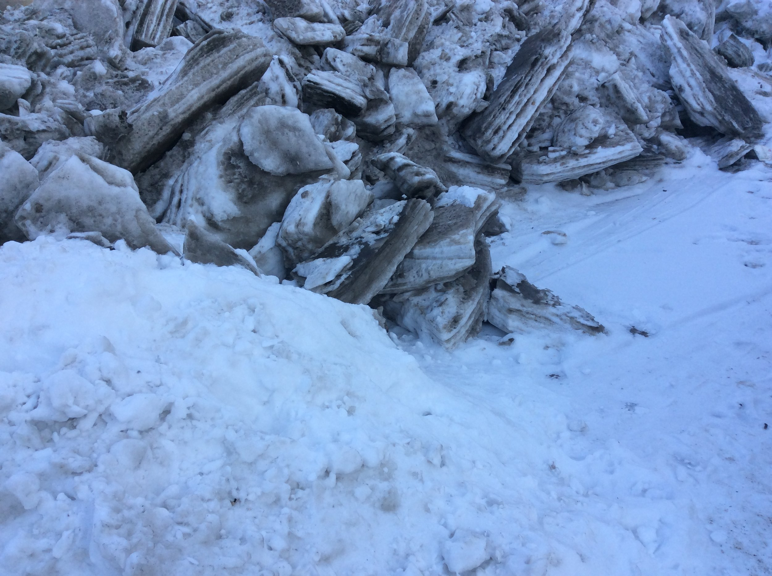 """The spring thaw means """"ice pyramids"""" everywhere: these chunks of ice spent the last five months coating a sidewalk. Now, they'll be scooped up and dumped outside from the city. The striations are mostly sand, which was poured on the sidewalks periodically to aid walkers in navigating the ice."""