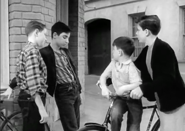 Beaver rides jauntily while Wally steers the bike, a very young HARRY SHEARER!