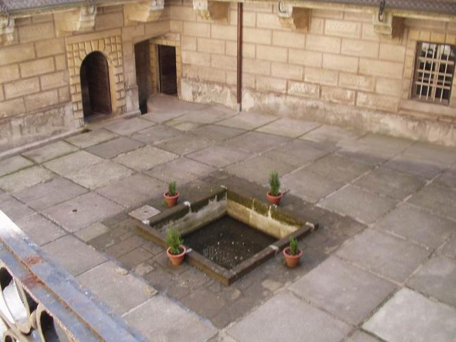 Shot of the center courtyard showing the drainage grate over the original fissure, filled in by rocks and concrete.  Some believe it's a water well or fountain, but those who visit don't seem to think so.  Photo by  No. 666