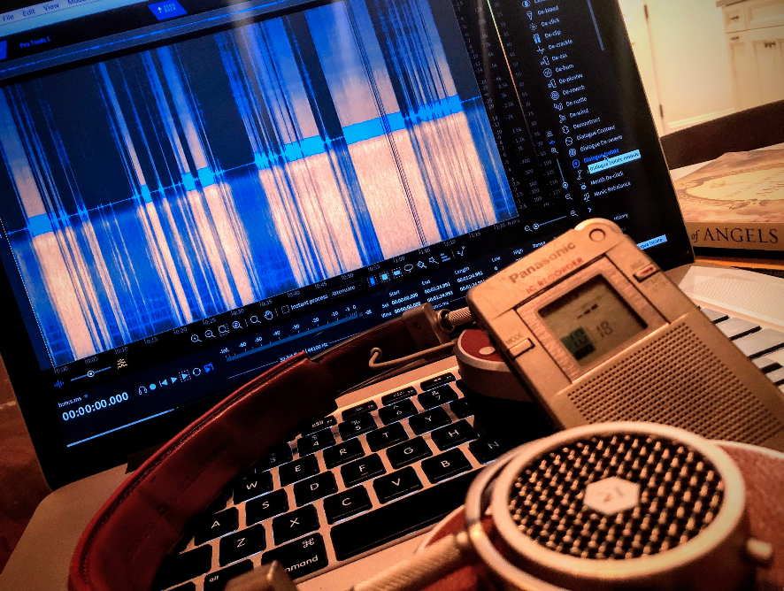 "A screenshot of the Izotope audio clean-up Plug-in called ""RX"" and its visual waveform.  In the foreground is the Panasonic RR DR-60 digital audio recorder."