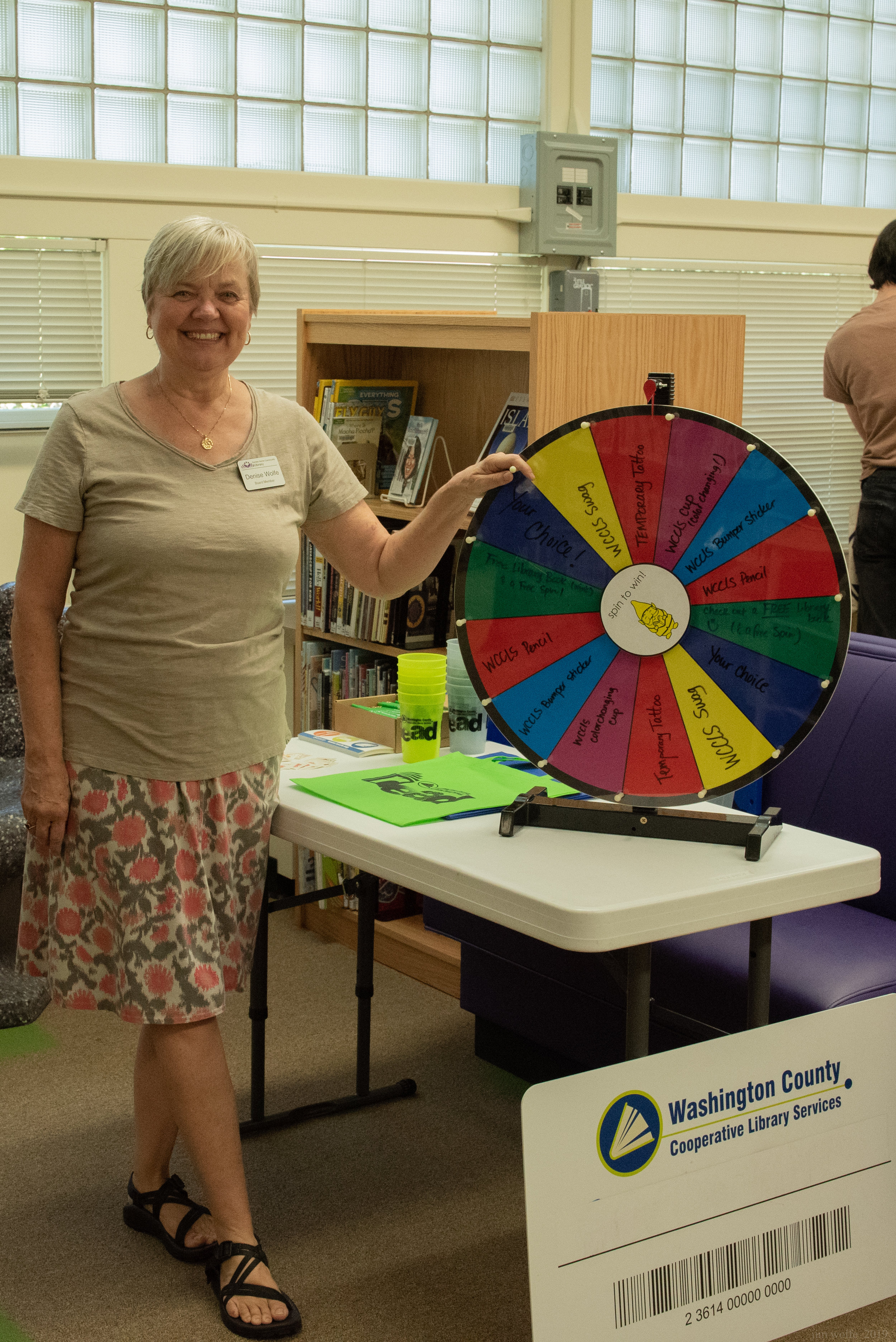 Board Member Denise Wolfe plays Vanna White at the prize spinner