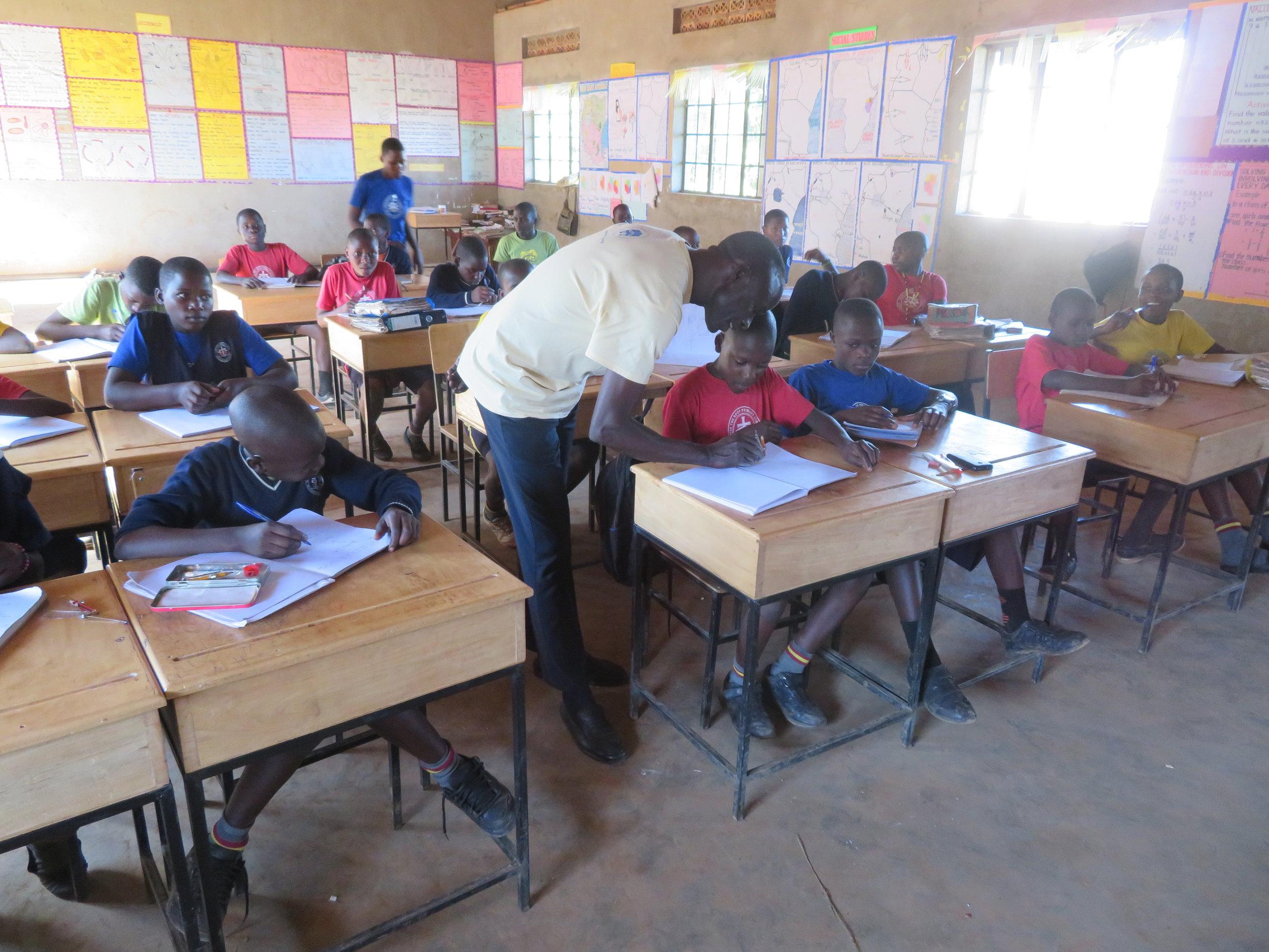 Teacher helps child with work.JPG