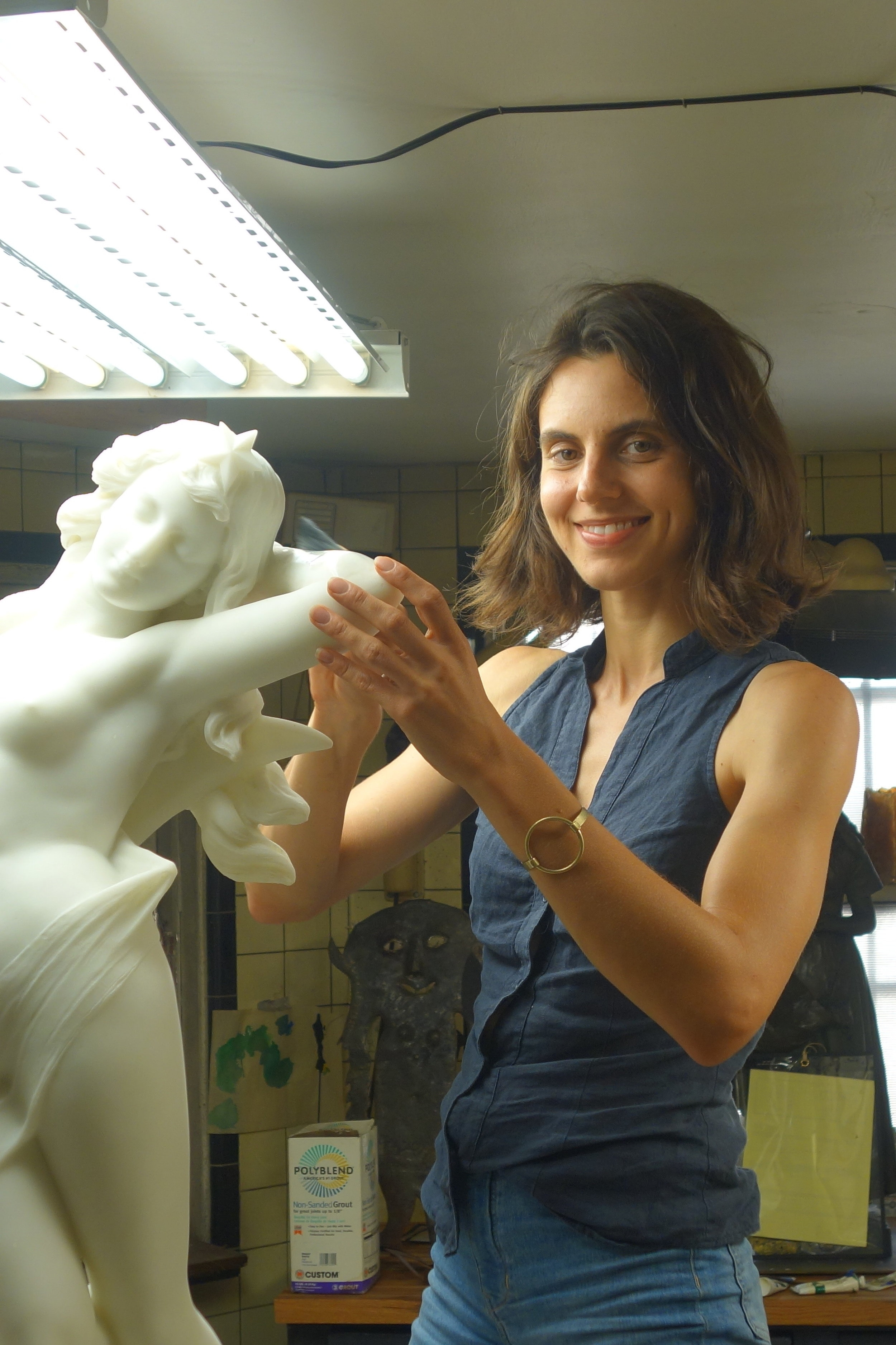 Jennifer Keltos circa 2018 detailing and carving hair on a marble statue.