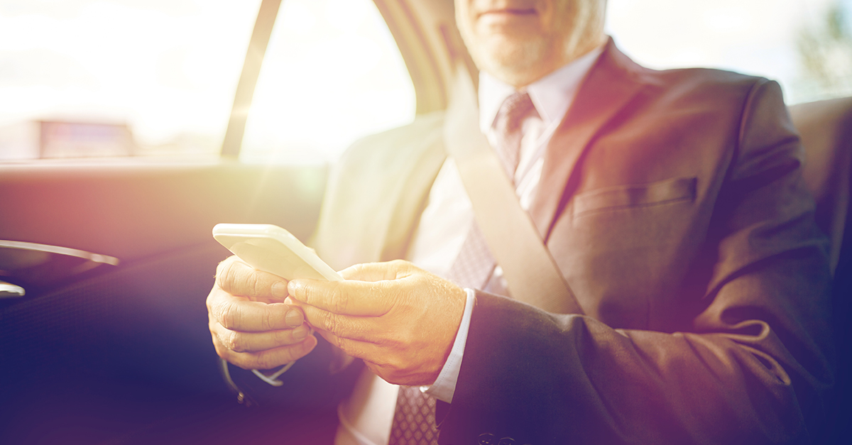 Sales manager riding in the backseat of a car, using his mobile device to access Epicor CRM/ERP data from anywhere using Bezlio.