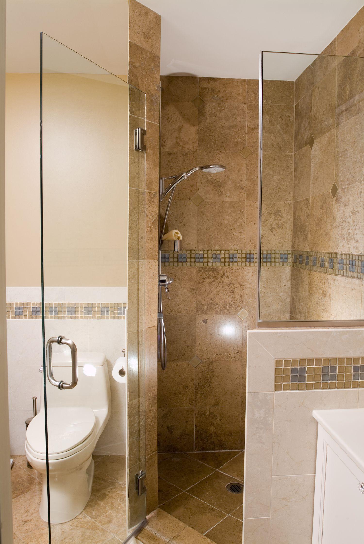 A corner shower with frameless glass doors