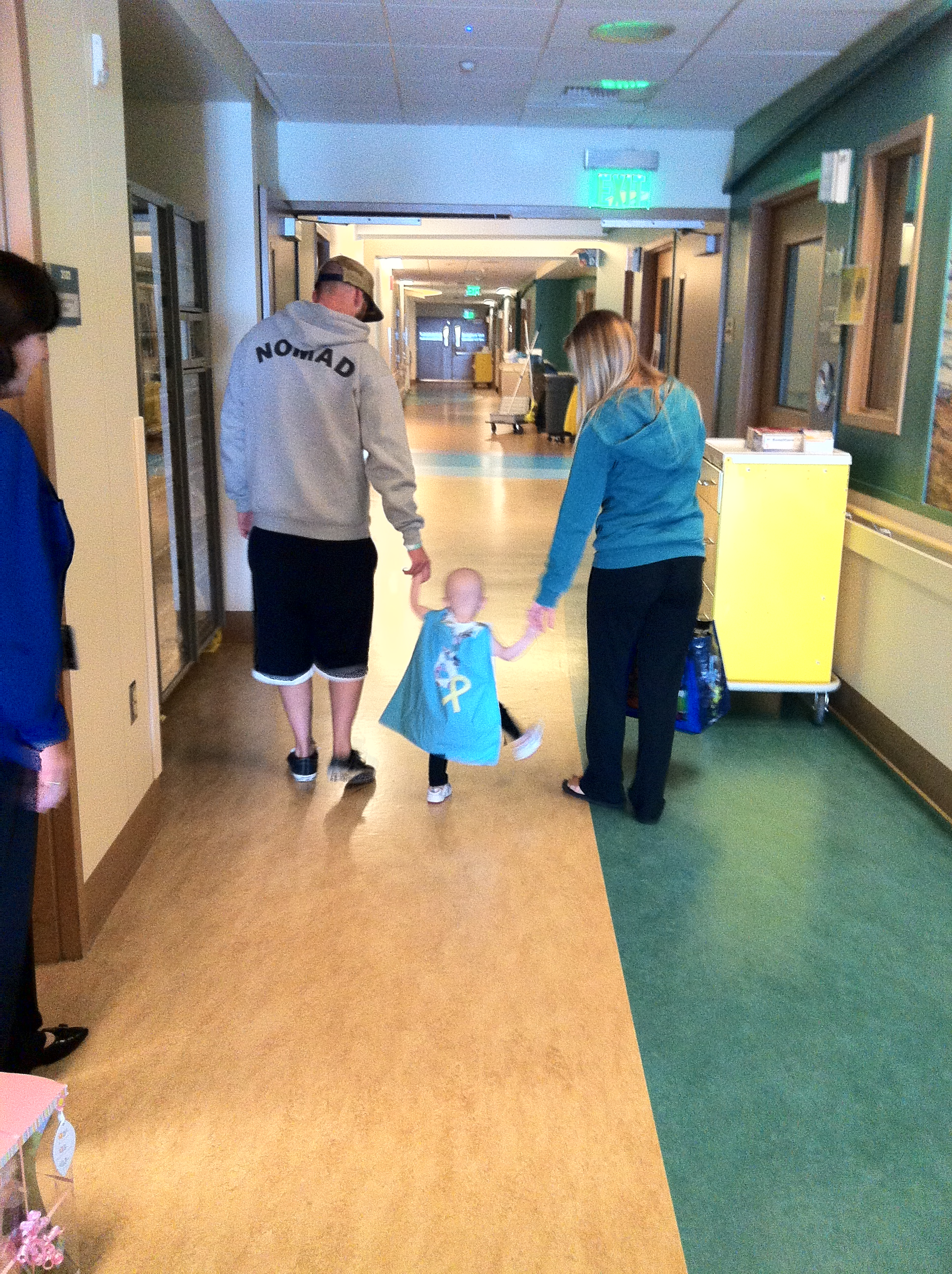 Brixton, happily walking the hospital halls with dad and mom in hand