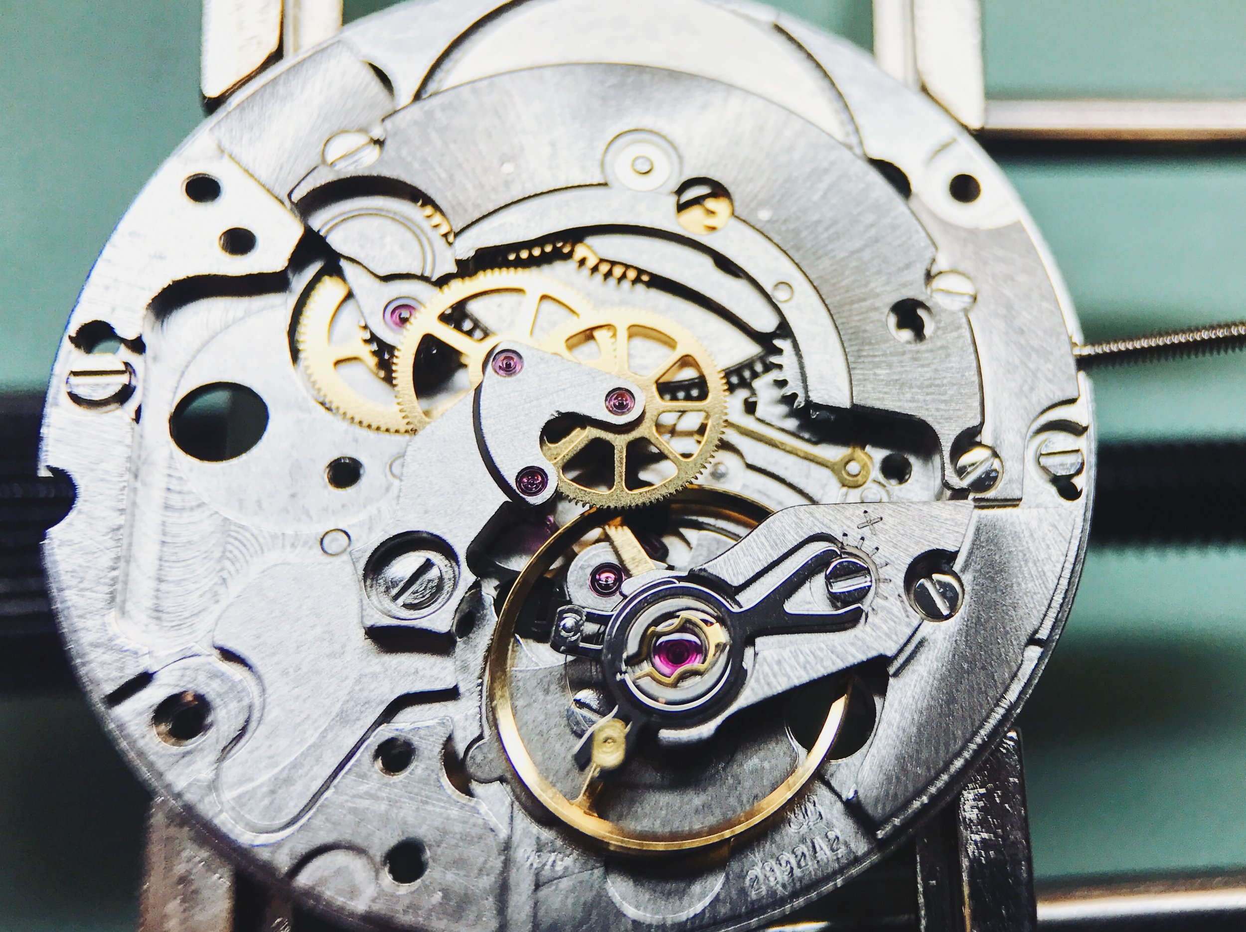 The lever, northeast of the balance wheel, is held in place by a hope and a prayer until the automatic module is installed to provide an axial bearing surface.