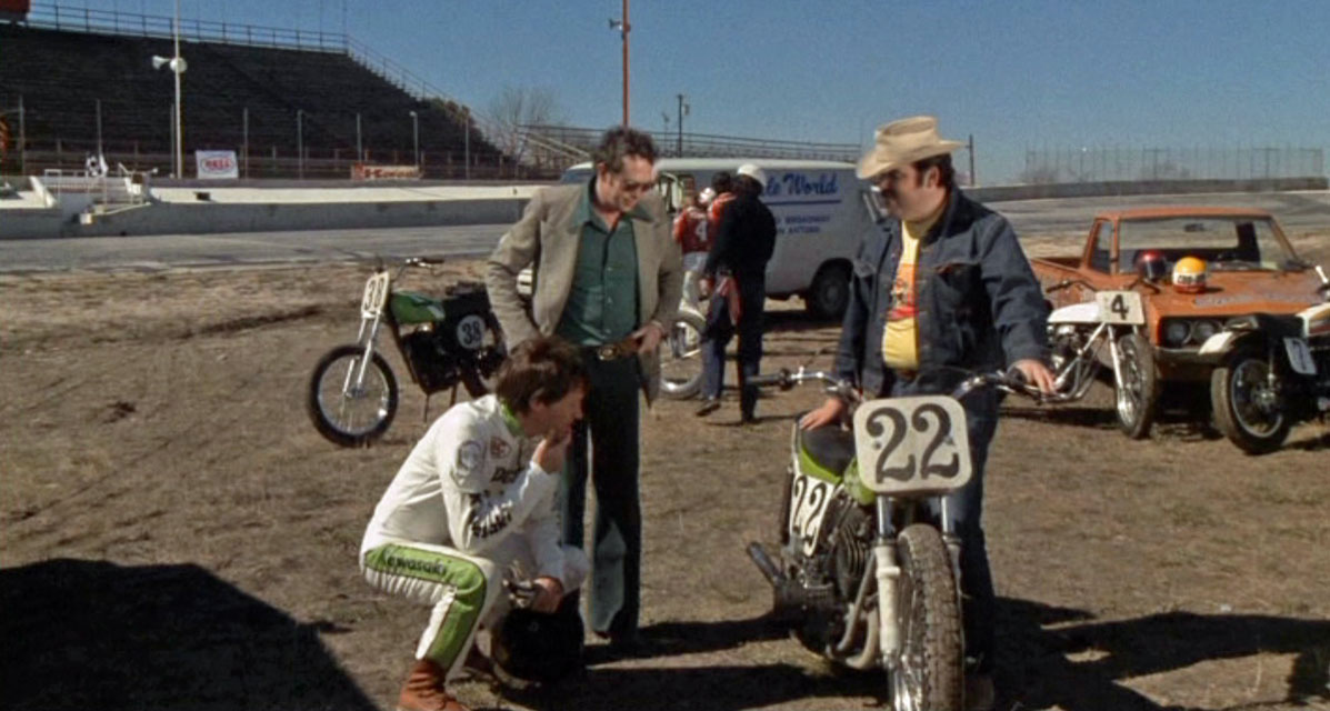Roger and Frank look at the motorcycle held by Cal Mathers at the racetrack. © 1975 Twentieth Century Fox Film Corporation