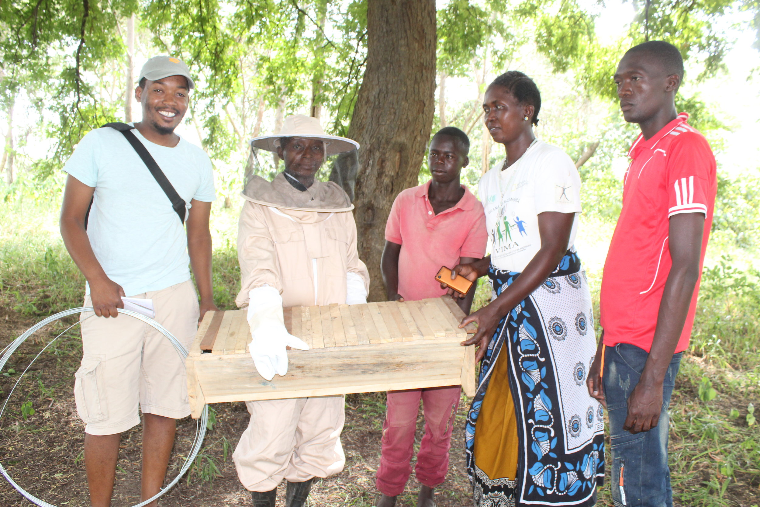 Emmanuel Stephen with the Mirumba Beekeeping Group during hand over of the beekeeping materials.