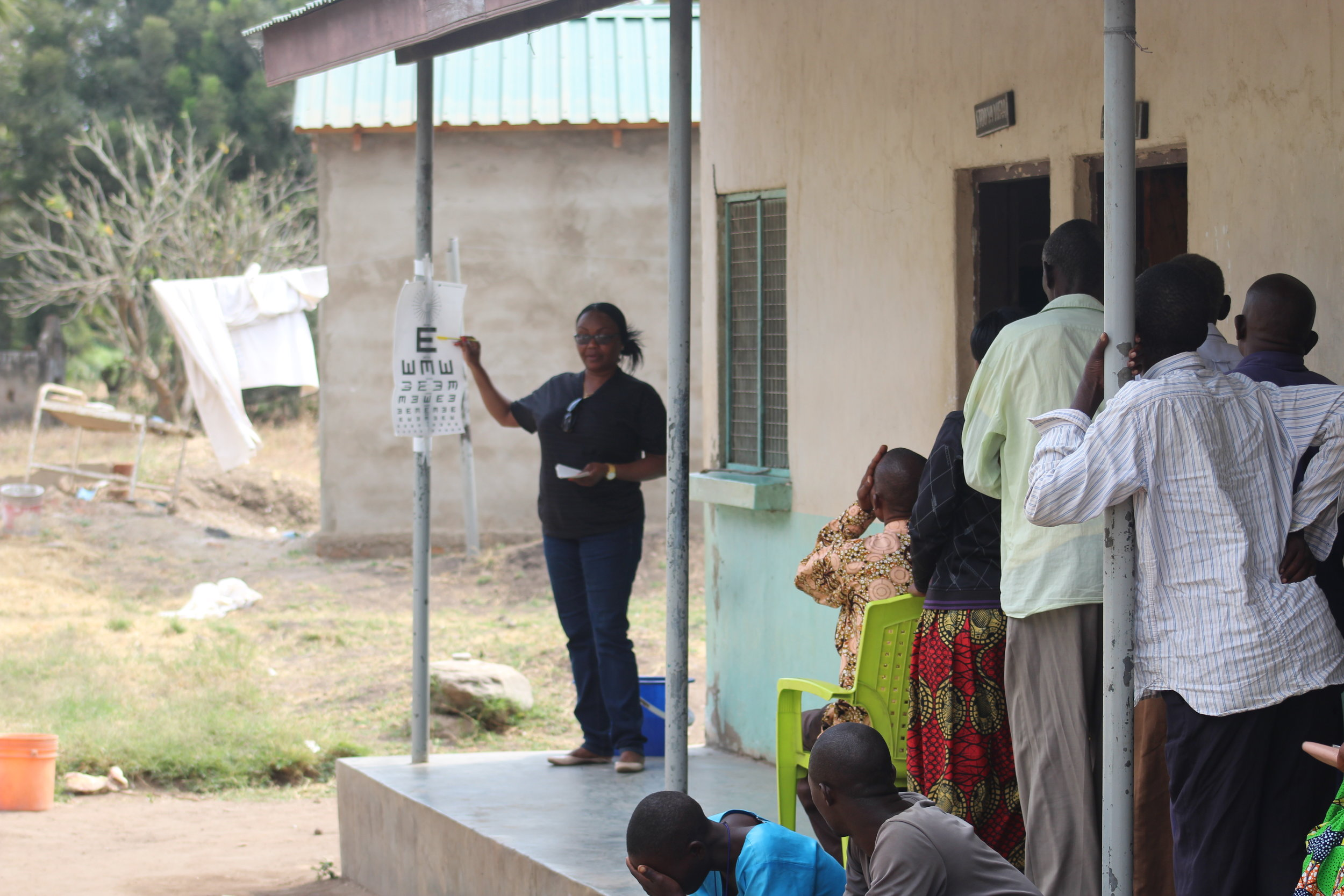 Dr. Upendo testing distance vision of patients during the eye clinic camp in Usevya