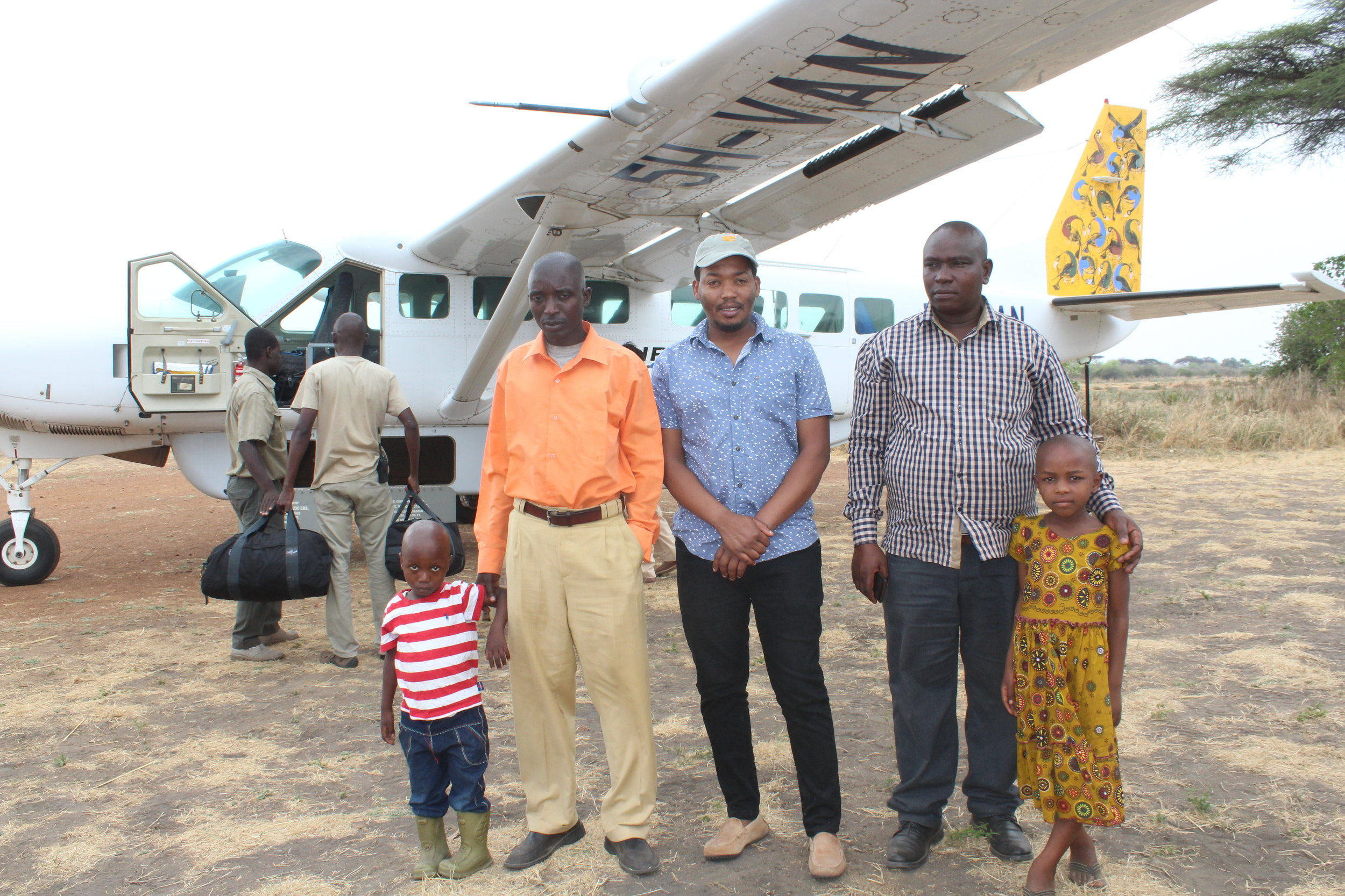 Emmanuel from LCMO with the children and their parents at Ikuu airstrip waiting to be flown to Arusha for treatment.