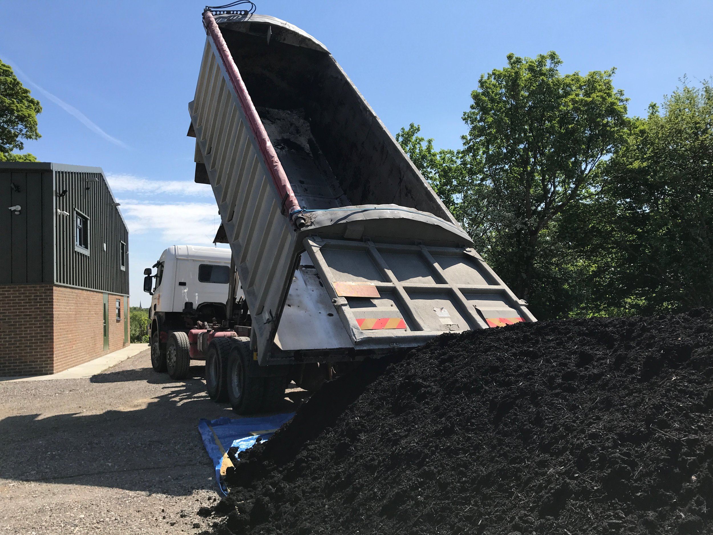 Since the soil on site has been essentially bare for a couple of years, we are giving it a boost of organic matter by spreading compost. It's a big job, requiring a spread of at least 50 tonne/ha!