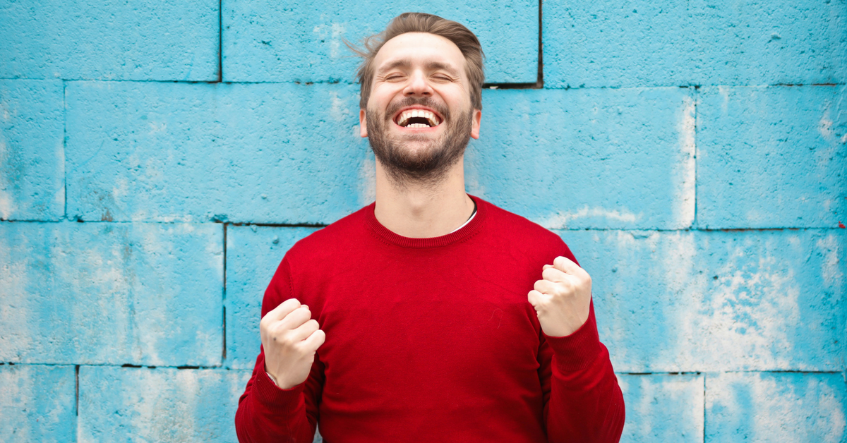 Man in red jumper laughing against blue wall