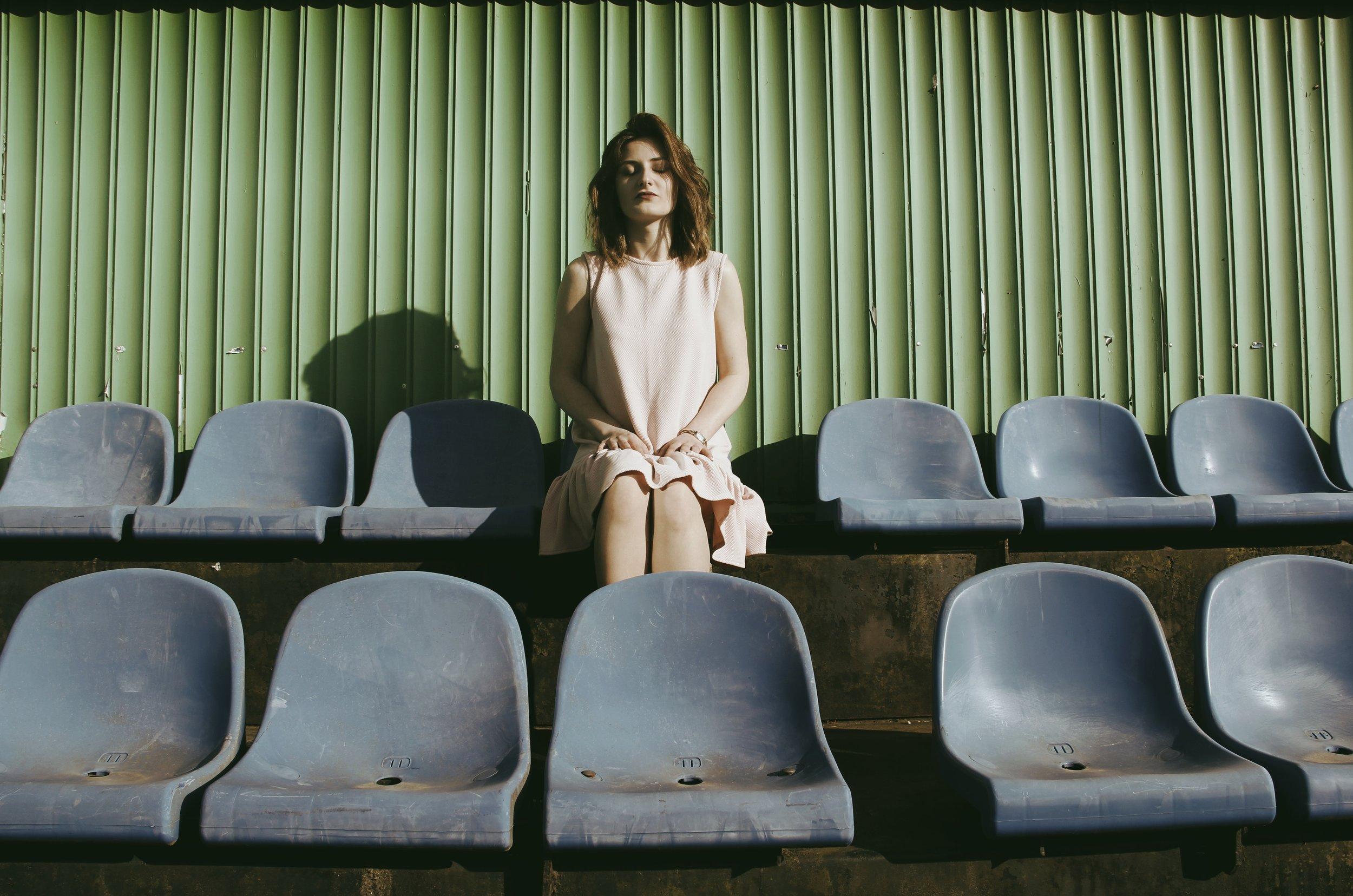 woman meditating on empty stadium seats