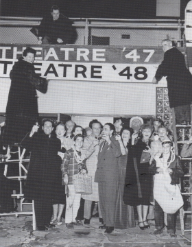 Margo (with fabulous fur coat) changing the theater marquee. Based on a theater she visited in Prague, she changed the name to the current year every New Year's Eve - a pledge to the public to present works commenting on the present.
