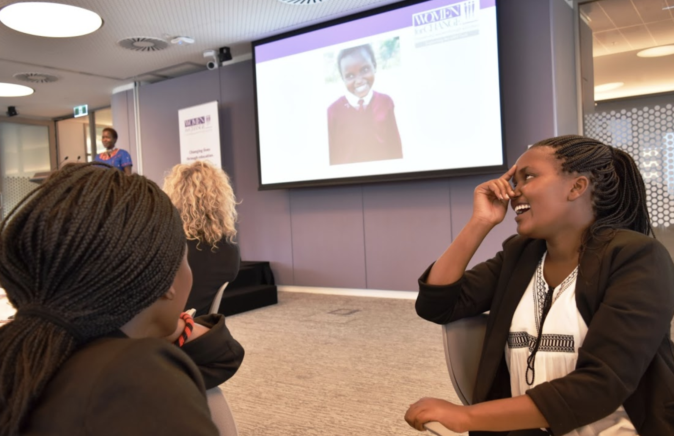 Linet laughs as Kakenya shares a photo of her as a fourth grader at KCE with the audience at the Women in Transactions luncheon.