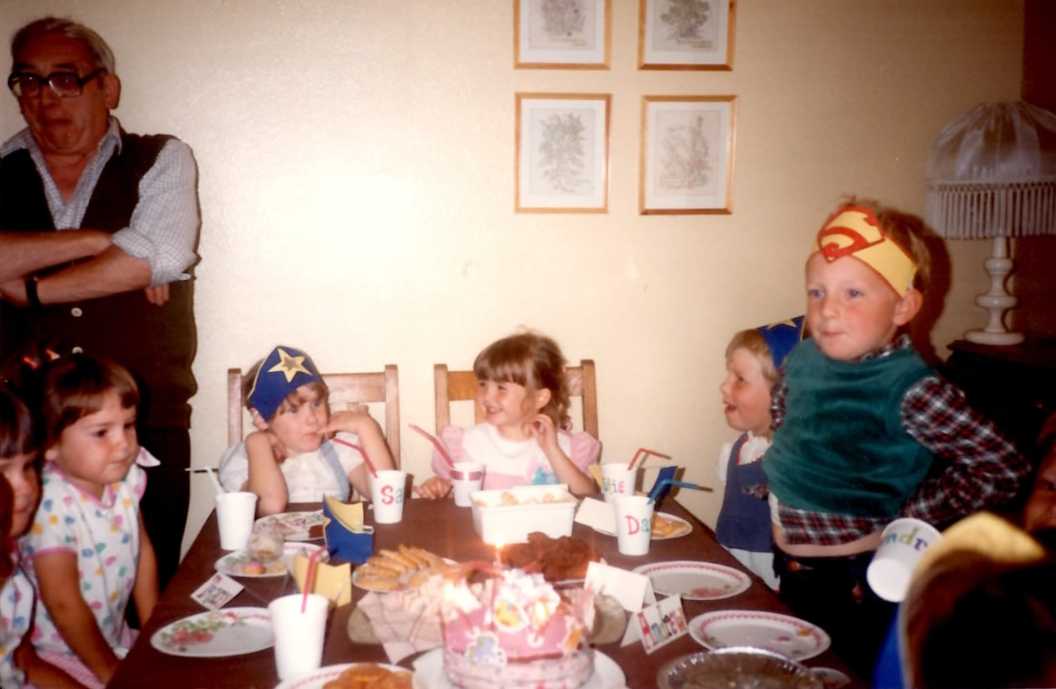 "That's me, top right with the mega-fringe! Check out my fabulous home-made birthday cake at the bottom of the picture, so much pink, I actually think it may have been My Little Pony-themed!  Also my wonderful Grandad on the left, drafted in to help ""supervise""………"