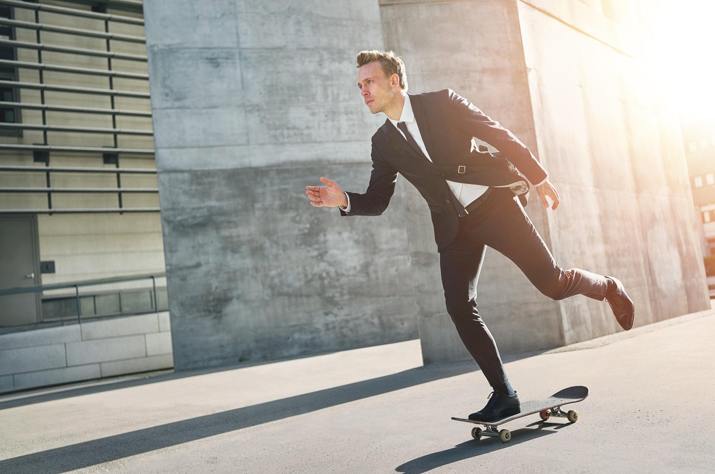 Suited-Man-Skateboarding-In-Sun.jpeg
