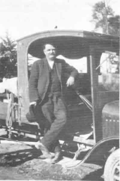 Cream Cart - Mr Jesse Seales in his first truck. The chassis was bought by his eldest son Bert, on his return from World War I and the cab and body were made at home. Mr J. Seales came to Oropi from Ngawaro in 1902. He was Oropi's first cream carter and mail man. He used a converted coach at first and later the truck in the photograph, though horses were still used to cross the gorge and when the roads were not bad.The cream cart was the only means of transport for setters in upper Oropi and grocery orders were left with the cream cans. Newspapers were yet another service. Rarely did the cream cart go down without at least one passenger for town. Mr Seales sons Ronald and Alex carried on with the cream cart until the early 1930's.