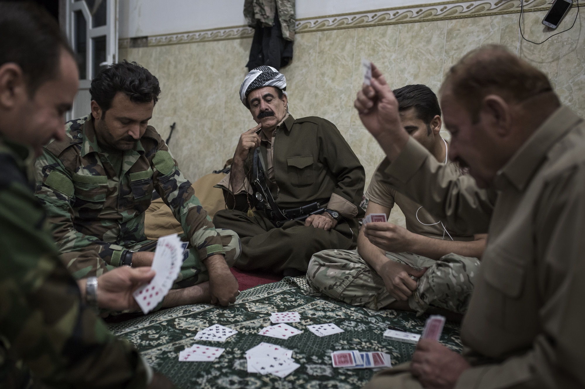 Peshmerga officers play cards the night before a Kurdish assault on an Islamic State held village.