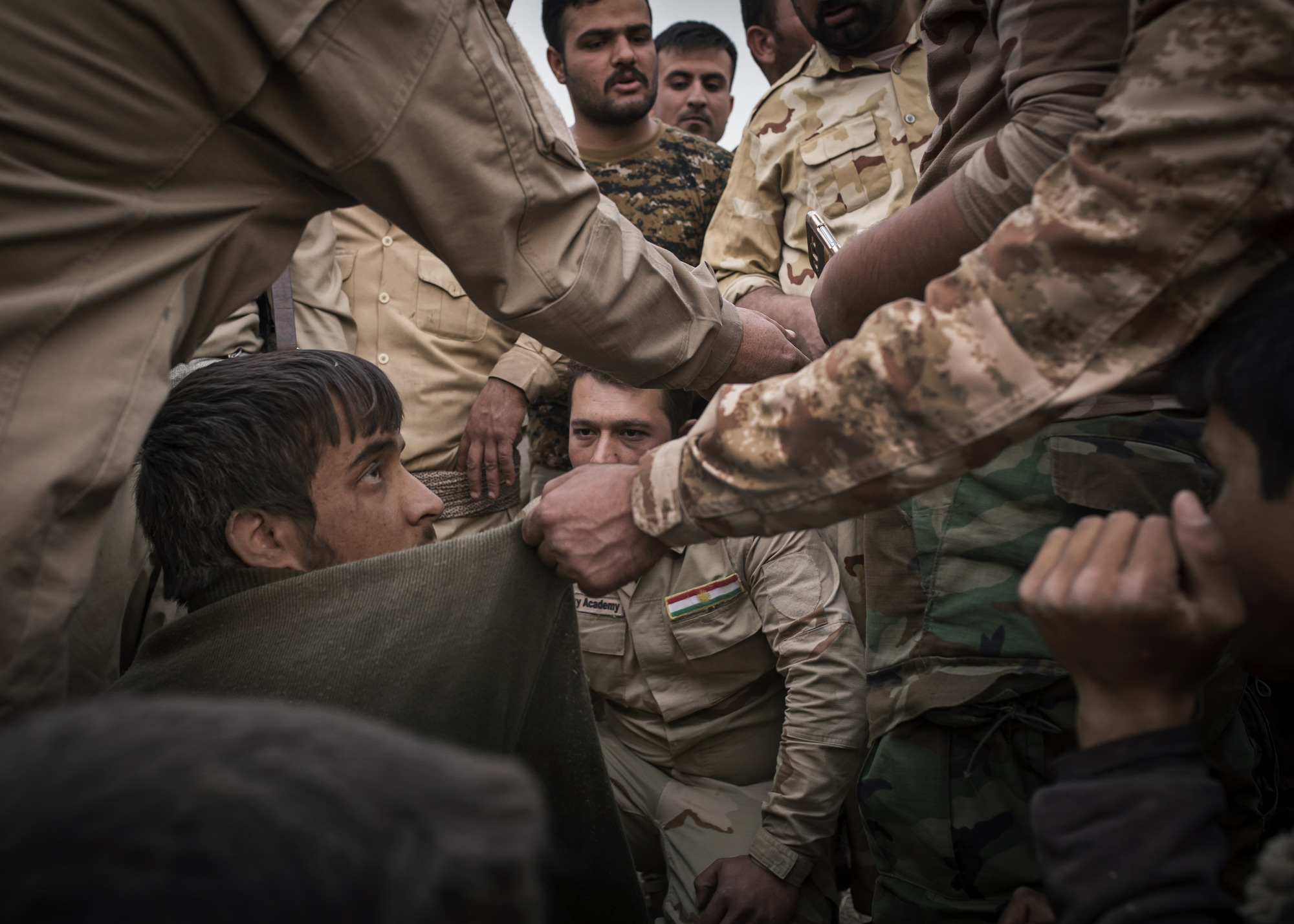 Three Arab boys are interrogated by Kurdish Peshmerga after they crossed a front line from Islamic State held territory.