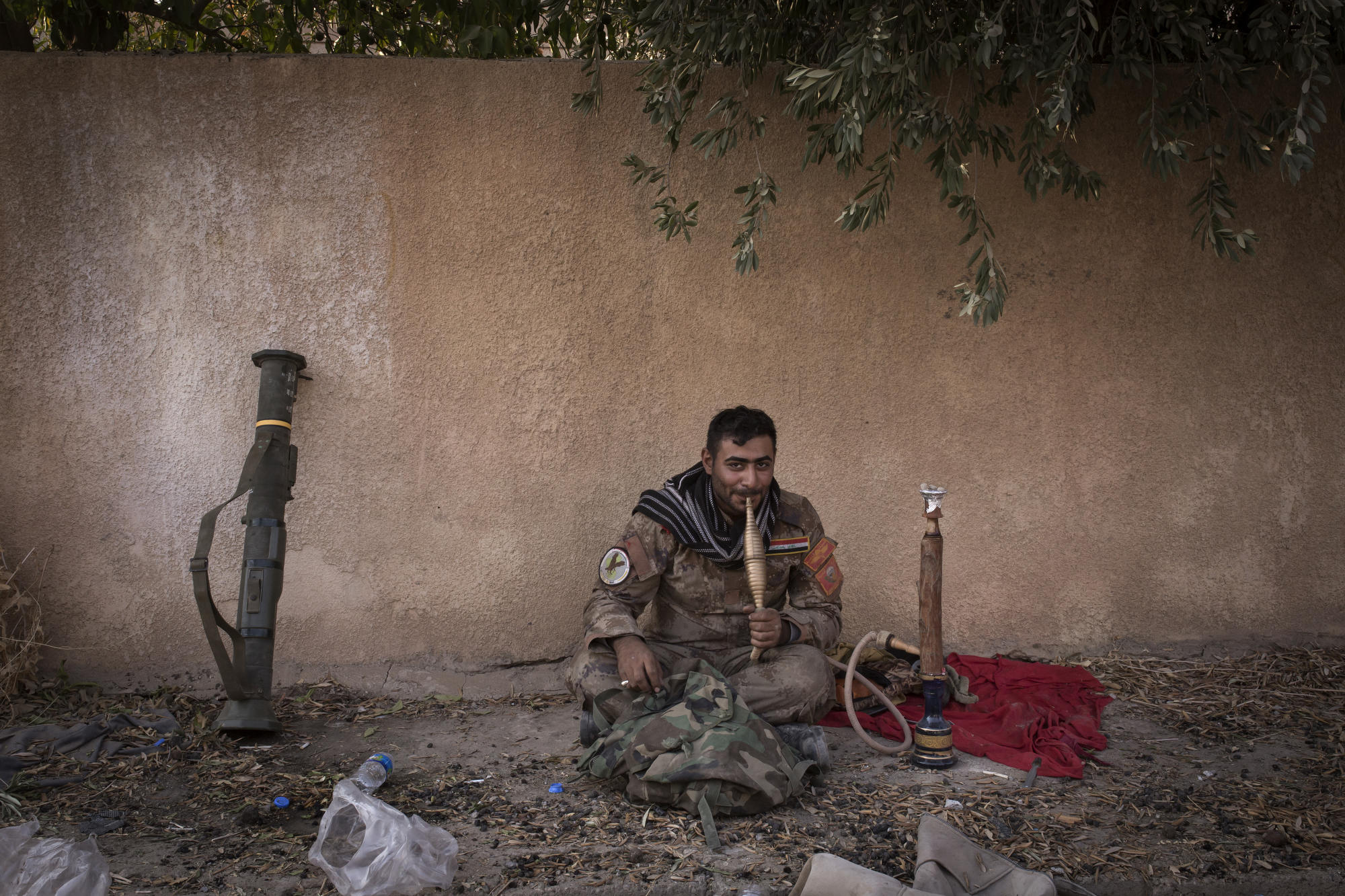 An Iraqi special forces soldier smokes a water pipe in the town of Bartella.