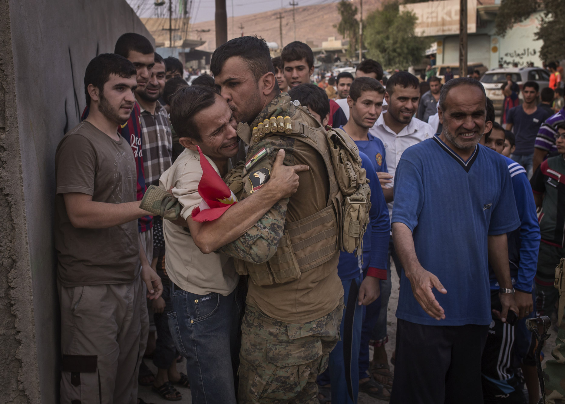 A local man collapses in the arms of a Kurdish soldier as his village is liberated from Islamic State control.