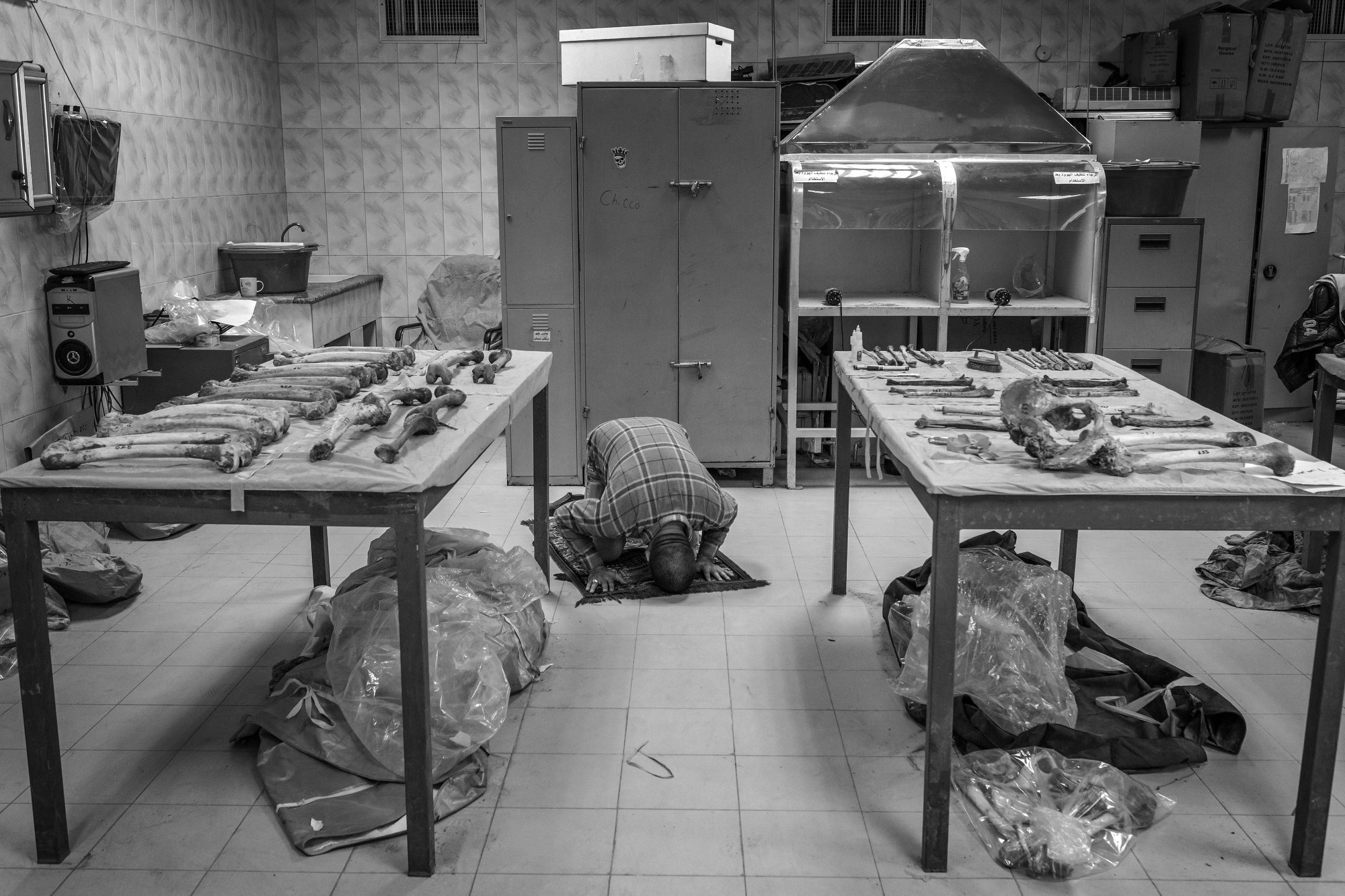 A worker prays at the Baghdad mortuary in a room full of human remains recovered from mass graves.