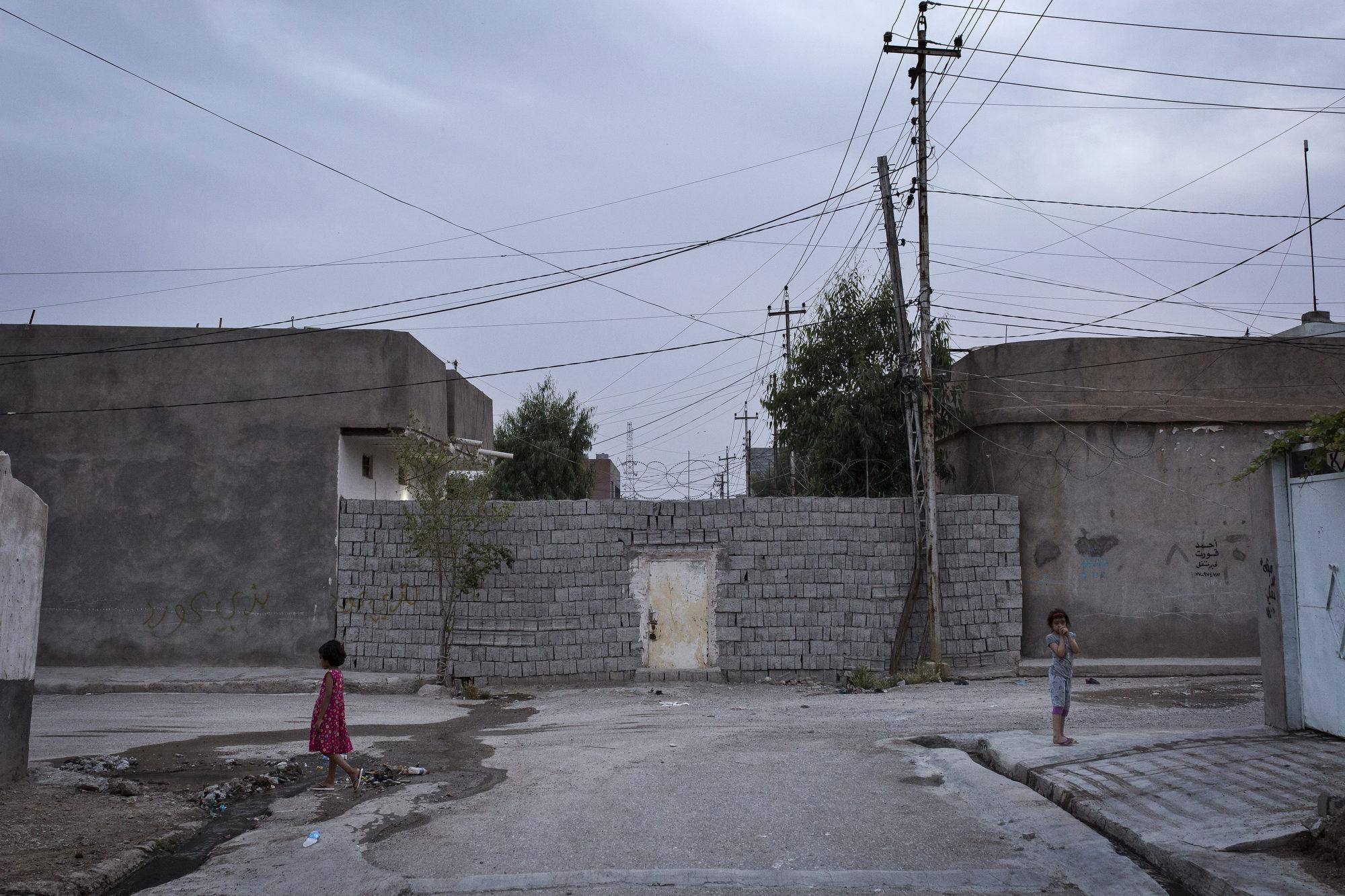 Children play near a wall separating Kurdish and Turkman areas.