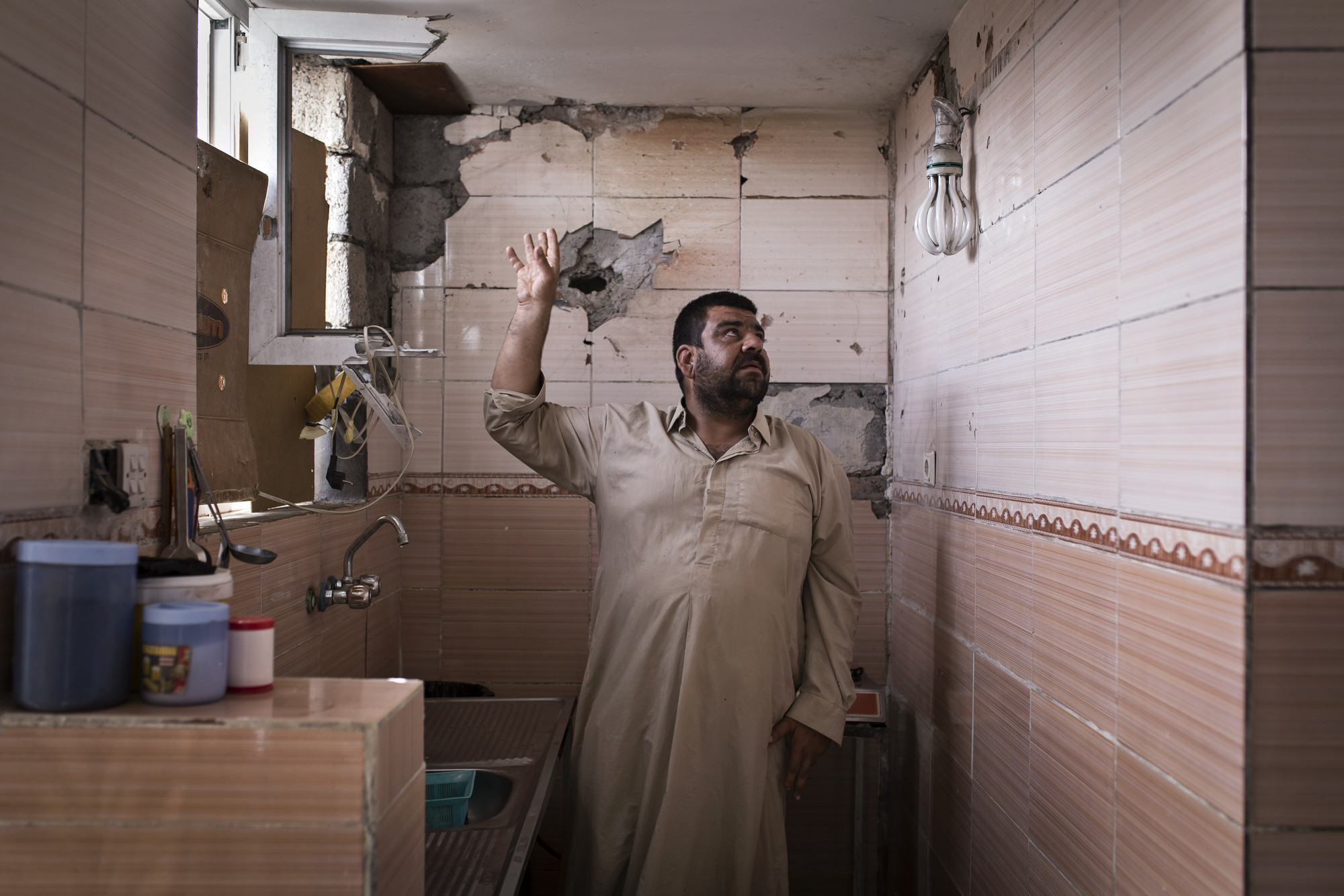 A Turkman resident shows damage inside his home which was allegedly hit by fire from a Kurdish tank.