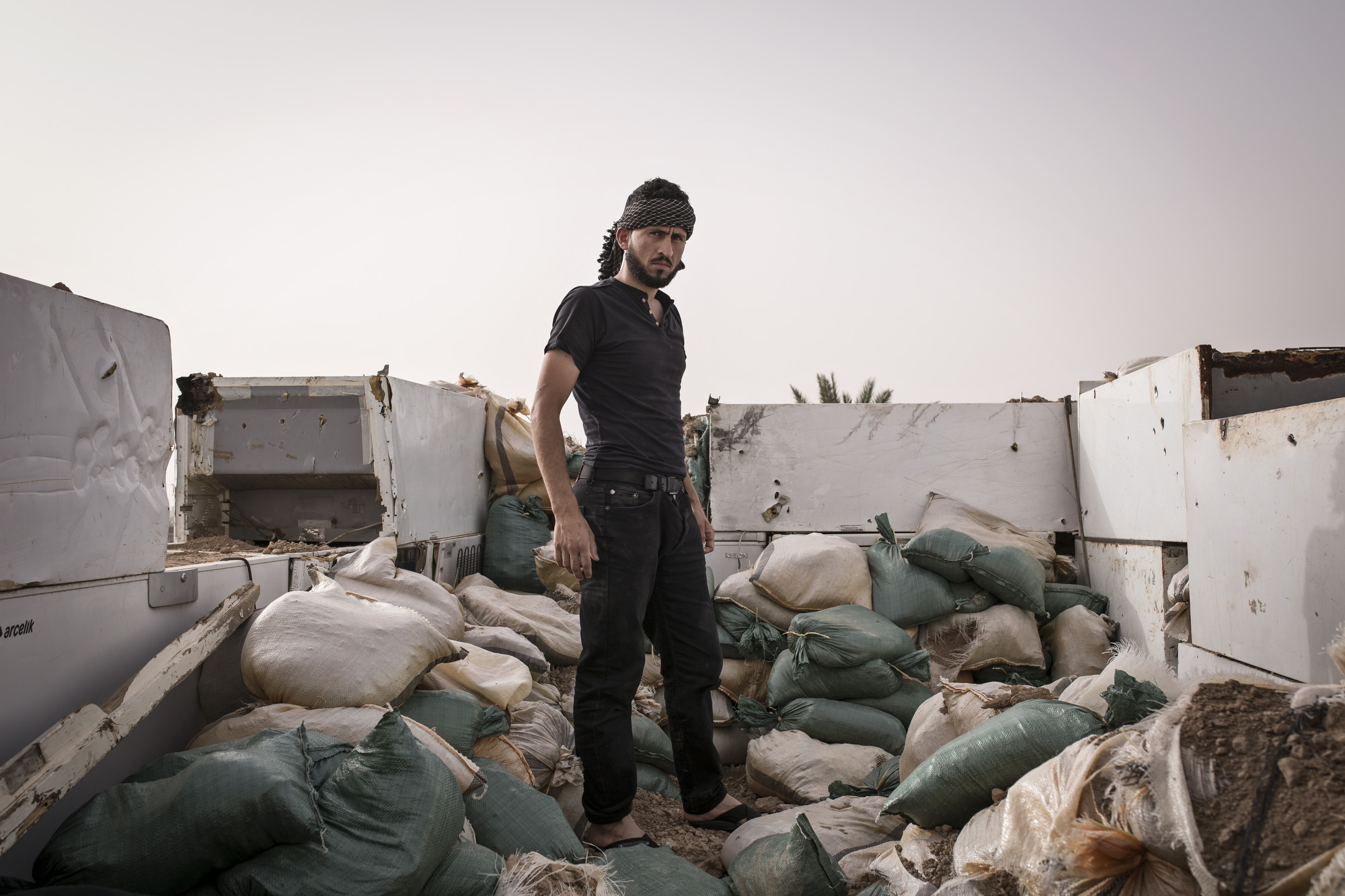 A Turkman resident stands in an improvised fighting position.