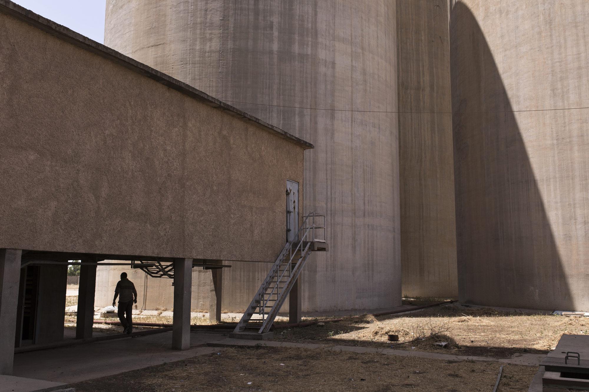A man walks through the site of a grain silo.